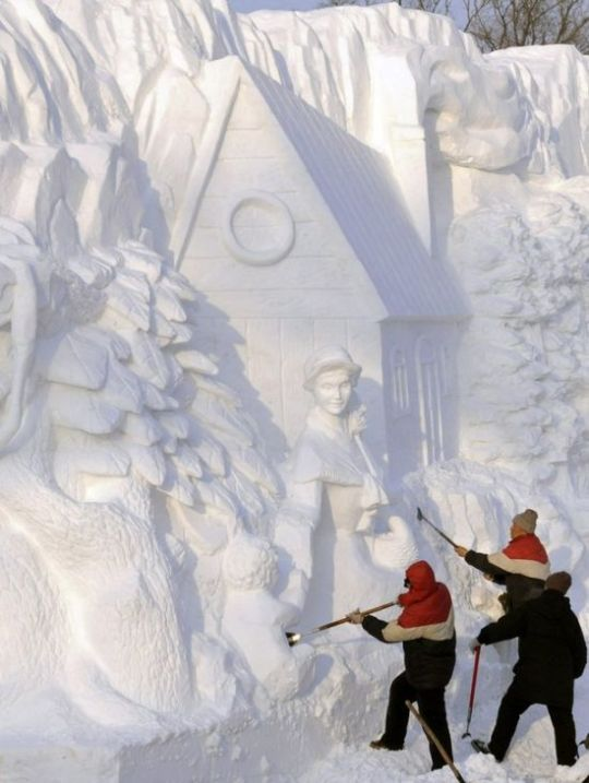 Workers shape a snow sculpture at the Harbin International Ice and Snow Festival in Harbin,